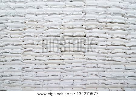 Many rows of plastic white sacks with goods are in big warehouse