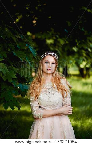 Pretty young tender blonde in a lace cream dress against the background of a garden