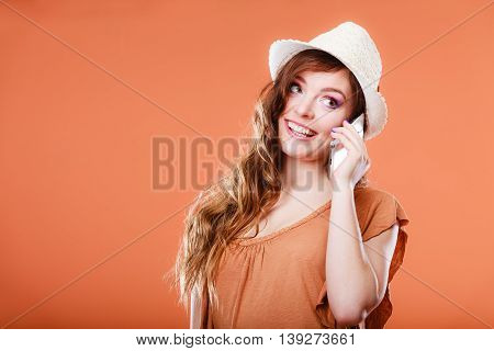 Technology and communication. Attractive summer woman talking on mobile phone orange background