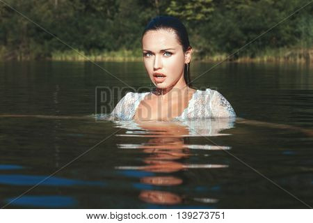 Woman emerged from under the water drops dripping from her face she was in the nature of the lake.