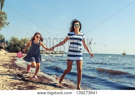 Happy carefree family running on beach at sea coast. Little girl kid with mother having fun. Summer holidays vacation. Happiness.