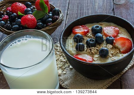 homemade oatmeal porridge with berries and glass of milk on wooden table, close up view. healthy breakfast