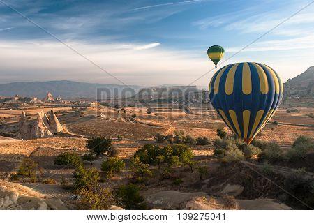 Balloons flying over Cappadocia at sunrise in autumn