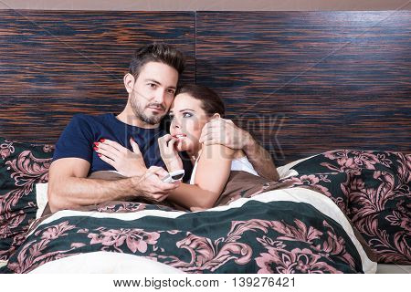 Beautiful young couple being scared in the bedroom.