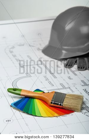 Construction of the building layout, building drawing on paper, paint brush and color samples, selecting paint colors, construction planning, building protective helmet and gloves, protective clothing.