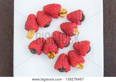 Red raspberries treats with walnuts, and chocolate chips laid out in rows on a white plate