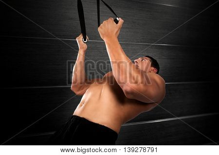 Muscular man workout with bandes of trx