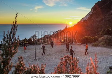 Mount Kinabalu Sabah Malaysia:March 12,2016:Undentified group of climber playing volleyball at Laban Rata built at 3,273 meter above sea level with sunset background.