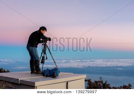Ranau,Sabah,Malaysia-March 12,2016:Silhouette of a photographer framing a shot, taking pictures at beautiful sunset on Laban Rata.This place is for climbers to rest before summiting the mount peak.