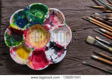 Brushes and colorful abstract colors painters used pallet on old wooden background