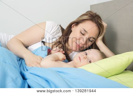 A happy family. baby and mother in blue bed