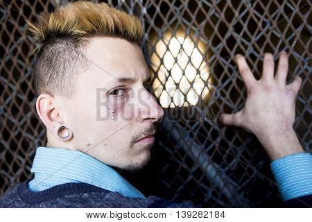 A young man revealing his sadness and depression against a chain link fence.