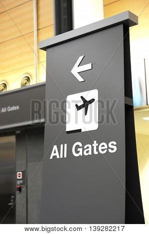 directional sign indicating airport gates for boarding