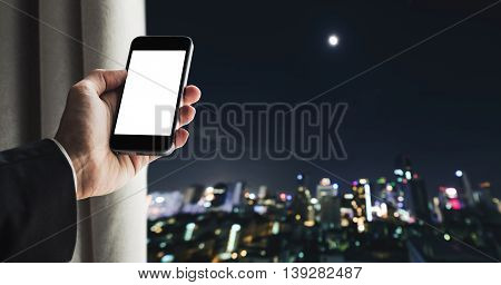 Businessman holding mobile phone with copy space on screen, and opening curtain defocus nightlife city view