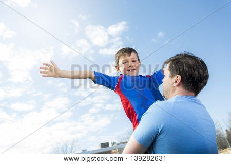 A man with with child playing football on football pitch