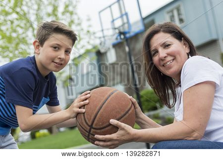 A Happy family having fun outside with a basketball.