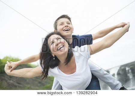 A mother and son playing in front of a waterfall