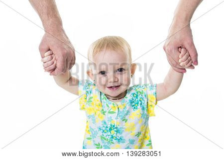 A baby taking first steps with mother father help on white background