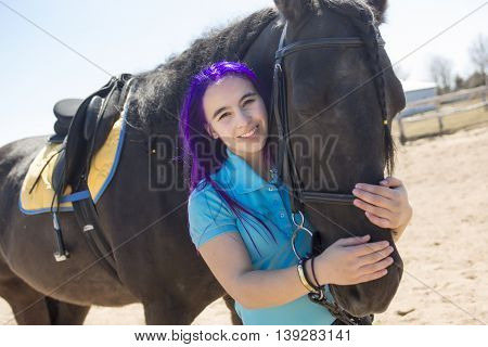 A Beautiful teen girl on the farm with her horse.