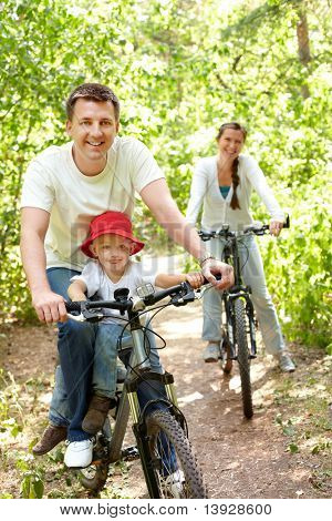 Portrait of happy man with son riding a bicycle in park on background of pretty woman