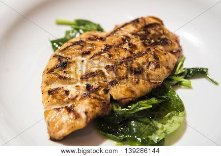 Grilled chicken breast served with steamed spinach