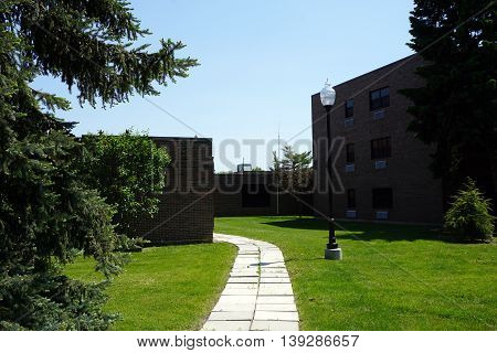 A walkway leads to a side entrance of the Saint Charles Borromeo Convocation Hall of Lewis University in Romeoville, Illinois.