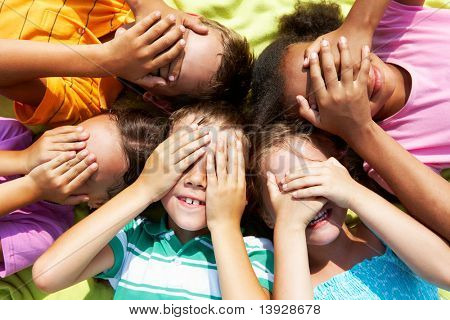 Portrait of happy preschoolers lying and closing eyes by hands