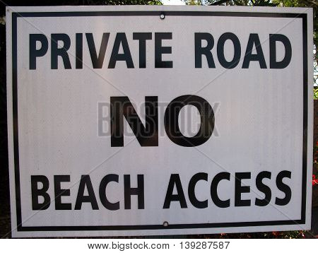 Sign reads private road no beach access with bold black and white letters near Malibu, California.