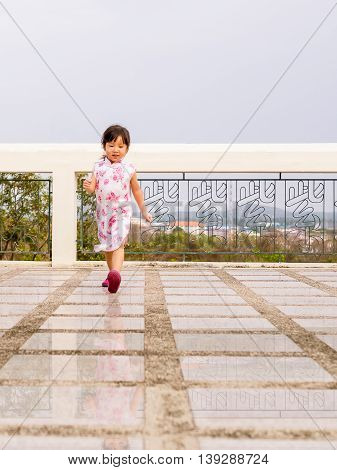 Happy kid asian baby child walking around action. qipao dress The chiness word is mean purple color