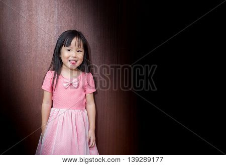 Portrait Of Asian Happy Little Girl, Stick Out Her Tongue