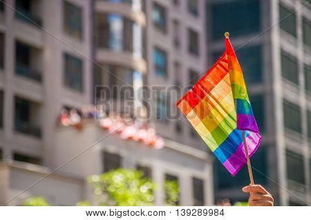 Hand holding a gay rainblow flag with copyspace