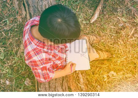 Top View. Boy Writing On Book. Education Concept. Vintage Style.