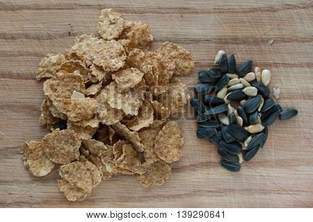 A mixture of grains nuts and flakes on a wooden background.