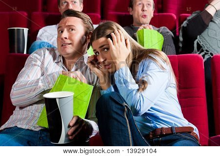 Couple in cinema watching a movie; it seems to be a horror movie