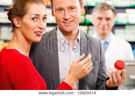 Pharmacist in pharmacy; in front customers - man and woman - he is holding a bottle with pharmaceuticals in his hand