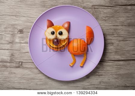 Cat made of fruits on plate and wooden desk