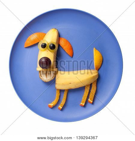 Happy dog made of fruits on blue plate