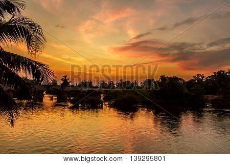 The sky blazes orange over a stone French colonial railroad bridge in rural Laos