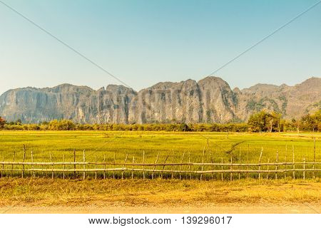 A wooden fence encloses a green field with cliffs in the distance in scenic rural Laos