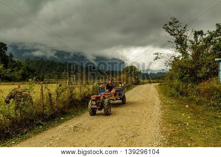 A farmer drives a tractor down a dirt road under a stormy sky in rural Laos