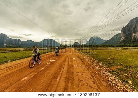 Bikers on a dirt road past the strange cliffs of Vang Vieng, Laos