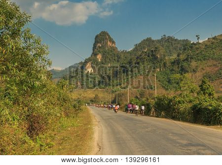 School children ride bicycles home among the strange cliffs of Laos