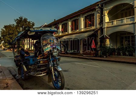 A tuk tuk parked on a street lined with French colonial buildings in Luang Prabang, Laos