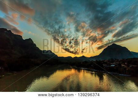 The sky and river glow orange after sunset in the countryside of Laos