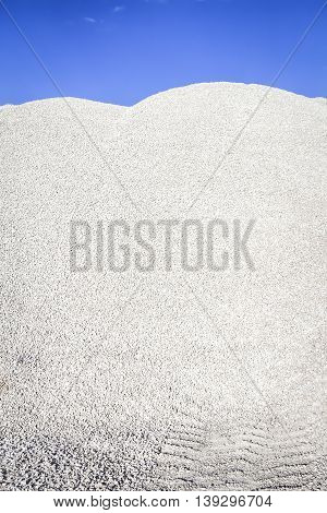 High mound of white crushed stone on a background of blue sky
