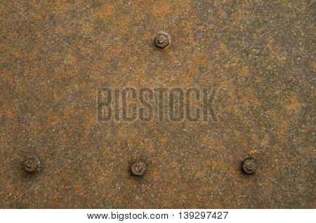 A texture of rust covering metal sheet and four bolts