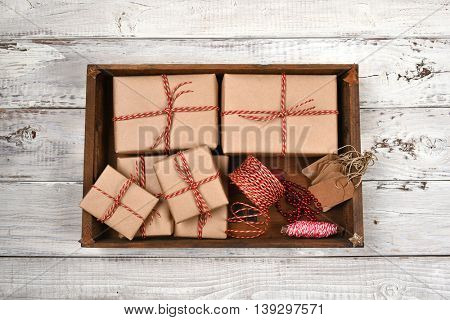 Wood box on filled with plain brown paper wrapped Christmas presents with twine and tags.
