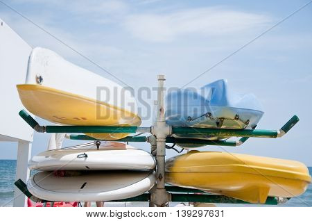 canoes of various colors lay in the sand