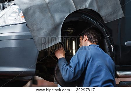 Mechanic inspecting car suspension system. Closeup of serviceman making diagnostics of automobile undercarriage