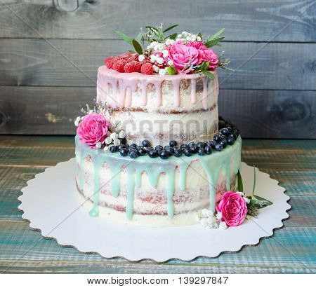 wedding color drip cake with roses blueberries and raspberries on wooden plank